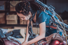 woman working on motorcycle.