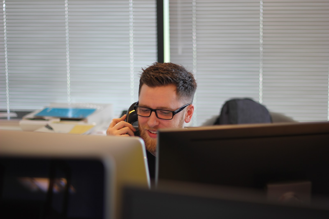 Man speaking on phone at desk.