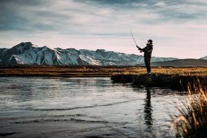Man fishing in lake by mountains