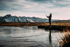 Man fishing in lake by mountains