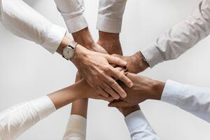 people with hands together on a team