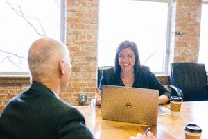 woman speaking with man at conference table
