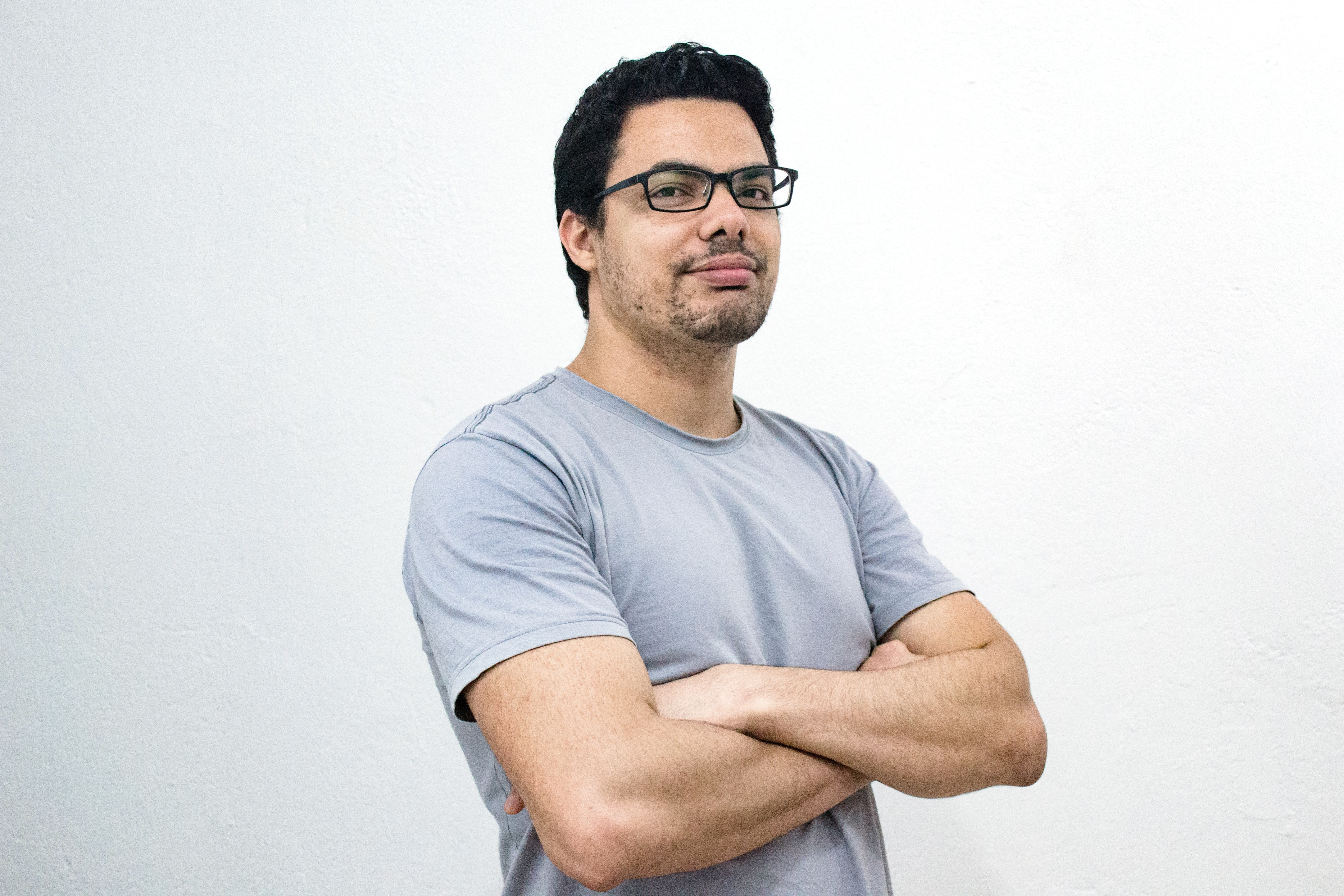 man in gray t-shirt with arms crossed.