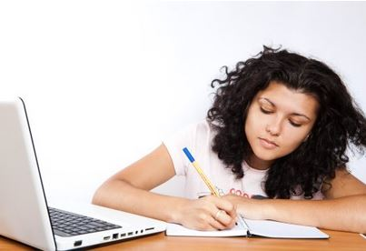 Student writing at a desk with a laptop